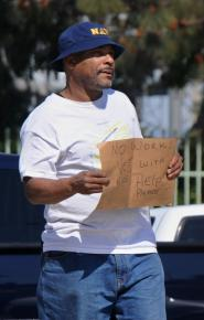 An unemployed veteran asks for money from motorists in Los Angeles