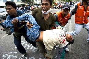 Thai Red Shirt protesters carry a man who was wounded when police opened fire
