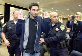 A UC Irvine student is escorted from a lecture hall after a protest against Israeli Ambassador Michael Oren
