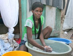 A woman displaced by January's earthquake washes clothes outside a makeshift shelter in Port-au-Prince