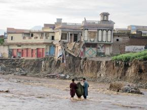 Two young men help an elderly woman along a flooded path in the Swat region of Pakistan