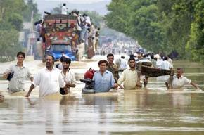 People fleeing rising floodwaters with what possessions they can carry