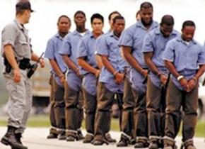 Shackled prisoners are led outside to begin a day of labor
