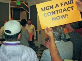 A manager at the Hotel Frank (in the white shirt) faces a protest by supporters of hotel workers