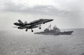 A $94 million F/A-18 Hornet flies past a U.S. warship