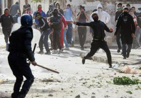 Protesters confront police during a street battle in Algiers