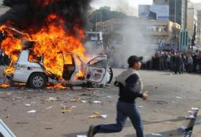 A car burns in the middle of the street as Libyans continue their mass protests against dictatorship