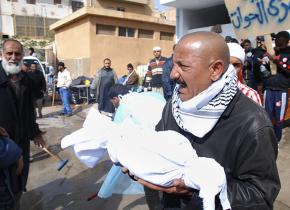 A man carries the partial remains of a fellow protester from a hospital in Benghazi