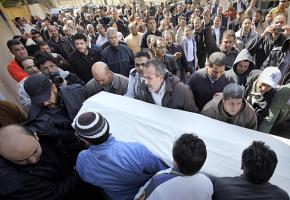 Mourners carry the body of a 44-year-old man killed in clashes with pro-Qaddafi forces in eastern Tripoli