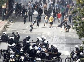 Protesters fend off a group of riot police advancing down the streets of Athens