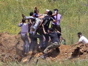 Protesters who marched to a fortified border fence with Israel carry a man wounded by IDF forces