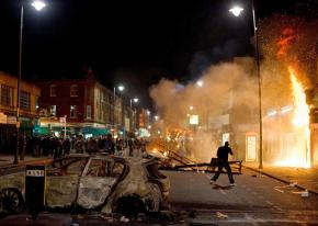 Police watch as rioters set a building on fire