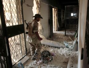 A Libyan rebel in Zawiyah guards an unexploded NATO bomb