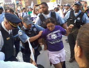 One of the undocumented youth who blocked traffic is led away by Chicago police
