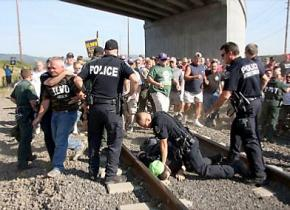 Police break up a gathering of ILWU protesters blocking the path of a train near the Port of Longview
