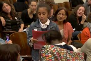 A third grade student uses the people's microphone inside the PEP meeting in New York City