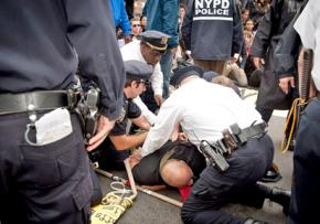 Police force a protester to the ground in the midst of the Wall Street occupation