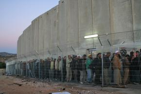 Palestinians wait in line before dawn to pass through a checkpoint outside Bethlehem