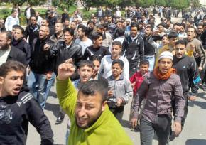Protesters marching through the streets of the Syrian city of Homs