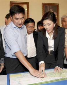 Prime Minister Yingluck Shinawatra (right) stands with conservative leader Abhisit Vejjajiva over a map of flooded areas