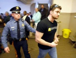 William Brown is led out of the town hall meeting by state police