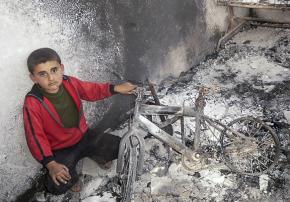 A boy in Daraa sits in the rubble of his damaged home