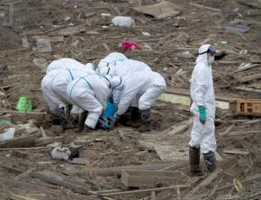 Worker sort through wreckage surrounding the Fukushima-Daiichi nuclear plant