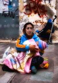 A single mother and her child survive on the streets of Athens