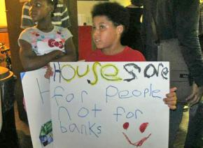 Children join in with hand-made signs at a Chicago town hall meeting
