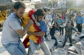 Aleppo residents carry a wounded child away from the site of government bombing