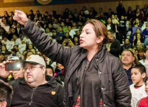 A Chicago Public Schools parent speaks out against closures at a packed hearing in Pilsen