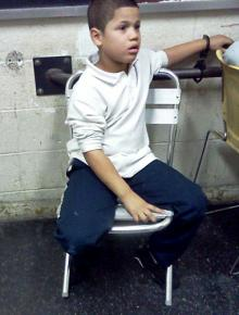 Seven-year-old Wilson Reyes' mother took this picture of him handcuffed inside a police station