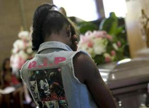A fellow student mourns at the funeral of a Harper High School student killed by gun violence