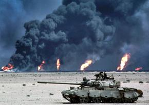 U.S. military forces roll by oil field fires in Southern Iraq in 2003