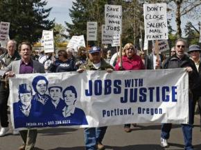 Demonstrators march to the Salem, Ore., USPS facility