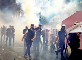 Turkish riot police march through a cloud of tear gas
