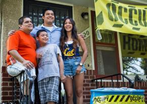The Ceballos family stands in front of their occupied home in Minneapolis