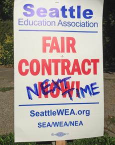 A union picket sign amended after ratification of the contract
