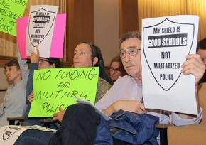 Activists with the Facing Urban Shield Action Network protest during a hearing in Oakland