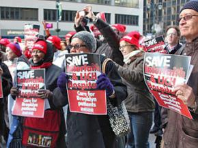 Interfaith workers and their supporters rally against the threat of the medical center's closure