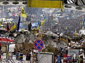 A dense crowd of protesters fill the streets beyond a barricade in Kiev