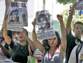 Protesters demand justice outside the courtroom where Grant's murderer went on trial