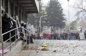 A confrontation between protesters and riot police outside a government building