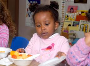 A child eats breakfast at a subsidized day care program for low-income kids