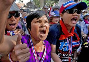 Anti-government protesters demonstrate outside police headquarters in Bangkok