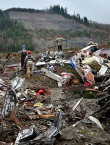 Rescuers search through debris in the aftermath of the deadly mudslide near Oso, Wash.