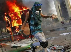 A student demonstrator sets fire to a barricade in Caracas