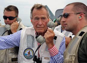 George H.W. Bush participates in a photo op aboard an aircraft carrier named after him