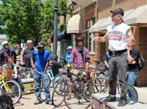 Jorge Mújica speaks to participants in a radical history bike tour raising funds for his campaign