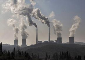 Smokestacks belch pollution at a huge power plant
